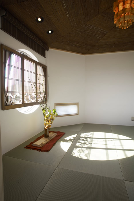 丸窓にお施主様が見つけた格子を組み合わせてエキゾチックな和室に。天井はスギ皮貼り。