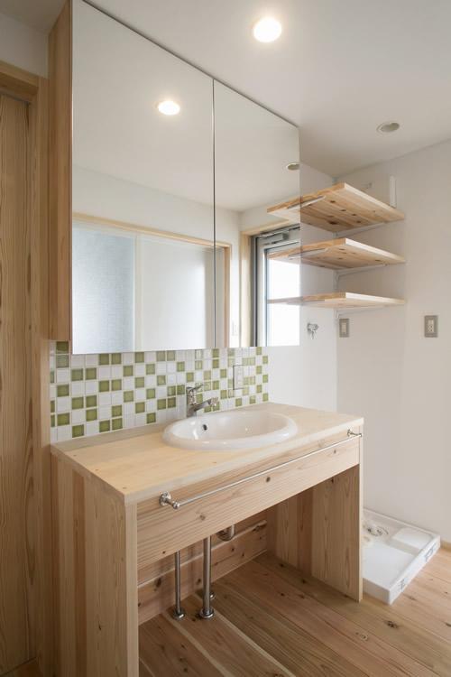 モザイクタイルが軽やかな造作洗面台、鏡の扉には収納も