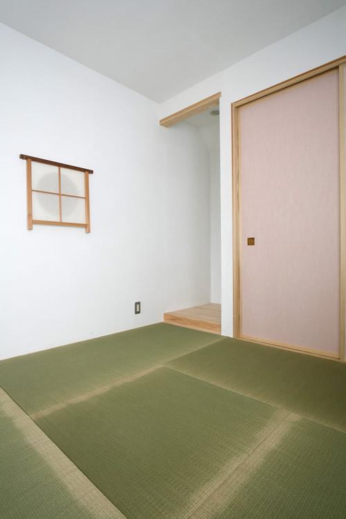 縁のない畳と淡いピンクの襖が現代的な和室空間